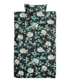 Sort/Grøn. Enkelt sengesæt i fintrådet bomuldskvalitet med trykt blomstermønster. Dynebetrækket lukkes forneden med skjulte metaltrykknapper. Et