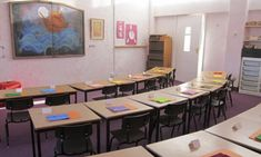 York Steiner School classroom, very plain and simple, small tables and dark pastic and metal chairs