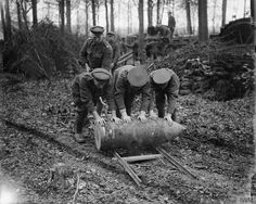 Gunners of the Royal Garrison Artillery in Englebelmer Wood moving a 15-inch howitzer shell by rolling it along a pair of rails. Sept 1916 at the Battle of the Somme.