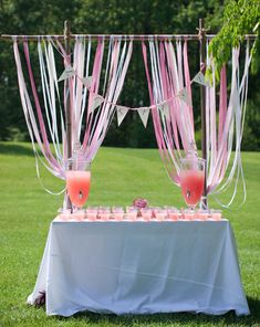 An adorable drink station is set up at Mimi and Harry's casual, outdoor wedding to help guests cool off before the ceremony. Large pitchers of pink lemonade match the pink palette of the wedding and quench everyone's thirst in the hot early summer.