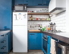 The clients loved the idea of having cool blue cabinetry to complement the gray concrete floor and the dark wood countertops.