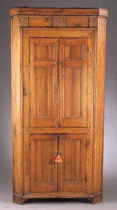 A Fine American Federal Pine Corner Cupboard, late 18th c., probably Southern, having a dentil-molded cornice above a reeded frieze, outset molding surrounding the paneled doors, the sides canted, raised on a molded bracket foot base, the interior with a warm honey red stain, height 71 1/2 in., width 34 in., depth 24 in.