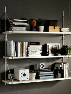 all-white ekby gallo shelving filled with books, a sound system and greenery. also love the binoculars!