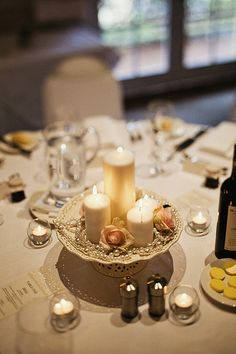 Tastefully done simple and elegant centerpieces. Candles, pearls, and fresh flowers
