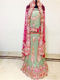 This green and magenta lehanga is perfect and a new combination.It is a hand embroidered bridal lehanga with usage of zircon ,stones ,thread and Zari.The fabric used is net,brocade and satin used for linings inside.It has a heavy embroidered blouse .