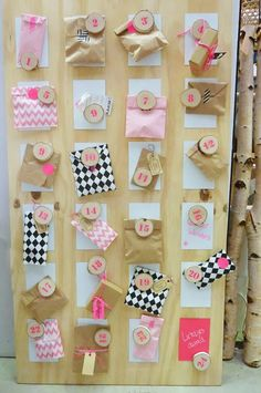 Calendario de adviento: Una combinación de sobres rosas y kraft en un tablero de madera, muy girly
