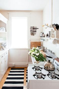 Small kitchen decorating ideas -- add a pop pf print and personality to any space with a bold cabana striped rug runner in black and white! We love it here in this small, all-white galley kitchen.
