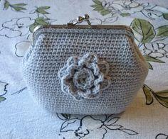 Virkattu kukkaro tai laukku kukkakoristeella.