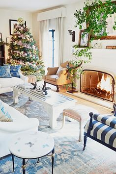Nothing beats a light airy white-walled living room with fresh greenery, pops of blue and a floral Christmas tree