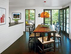 Cork floors, a black-and-white palette, and CaesarStone countertops that mimic honed concrete give this space in a Michiana home a modern edge, while horizontal paneling helps maintain a cozy cottage feel. Glass-paneled doors provide access to the deck and screened porch and also bring in light.