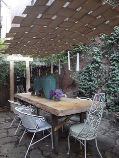 Cortney and Robert Novogratz used wooden planks to create a woven covering for this urban outdoor dining room.