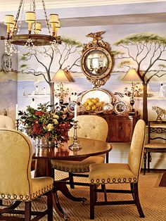This dining room in Dallas features a hand-painted Raj-inspired mural and custom balloon-back dining chairs covered in linen. (The linen has been gauffraged with a botanical pattern resembling damask.) An antique tole-and-crystal chandelier lights the room. A festive floral arrangement is all it takes to update this dining room for the holidays. (Photo: Tria Giovan)