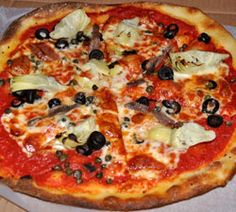 Fusaro's  Puttanesca Pizza, a puckery mix of capers, anchovies, and olives, with artichoke hearts and fresh mozzarella over the plum tomato sauce.