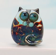 An ammusing cat bead whos shiny eyes are looking skyward in the most innocent way. Made on a base of transparent lilac the speckled body decoration has many colours to it, the splendid tail has a metallic shine. 25mm tall by 22mm at its widest point. From front to back at the nose area is