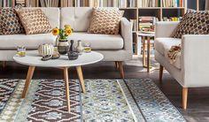 Witte salontafel met houten pioten en decoratie op het tapijt