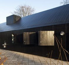 This pavilion is clad in charred timber but its polished steel ends reflect surrounding trees.