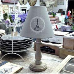 Prowansalska lampa stojąca posiadająca prostą drewnianą podstawę, oraz szary abażur z motywem wieży Eiffla, który dodaje jej wyjątkowej elegancji.