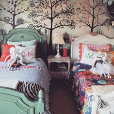 Gorgeous whimsical bedroom for two little girls. Green bed, white bed, floral wallpaper.