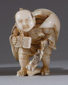 IVORY NETSUKE Early 20th Century Depicting a student carrying a paper lantern and books.