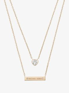 With two high-shine chains—each anchored by a chic, feminine pendant—this necklace is double the style statement. Its glimmering heart-shaped stone and sleek logo bar play against each other to create a quietly eclectic effect of layering in one step.