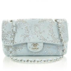 This is an authentic CHANEL Denim Quilted Swarovski Crystal Flap 10A.   This stunning flap bag is beautifully crafted of fine pale blue denim studded with Swarovski crystals in the form of Chanel CCs.