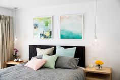 Romantic and fresh bedroom colour palette of mint green, teal blue and blush pink. Love the mis-matched artworks above the bed and those concrete pendant lights. See all the photos >>>