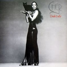 Cher as a cat like woman wearing sheer black gown