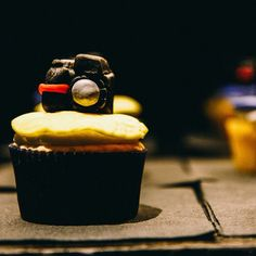 Photography Theme Birthday Cupcakes  Coconut Cupcake with Coconut Rum Butter Cream Icing topped with a fondant Camera.  ~Life is short...Eat dessert first~