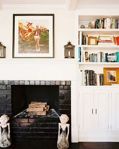Brick fireplace painted glossy black with white built-ins