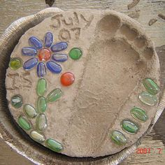 See a picture of a home-made garden stepping stone submitted by Jennifer Super. It features a footprint design along with glass bead embellishments.
