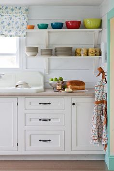 Farmhouse sink, white cabinets, open shelving, colorful bowls, and a little turquoise trim!