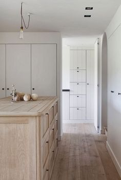 Scandinavian style kitchen with raw oak flooring and island paired with v-groove soft grey cabinetry.