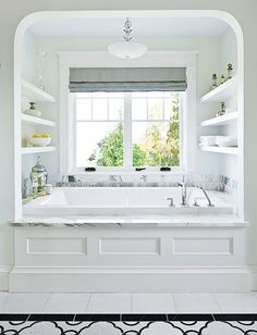 Now this is a tub! The deep BainUltra tub tucked under a window + the minimalist shelves + the mosaic floor tile = perfection. - Traditional Home ® / Photo: John Granen / Design: Susan Marinello