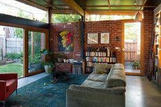 Warm walls, bookshelves, mossy green rug, tall windows and sun. Small House Swoon Florence street Nest Architects