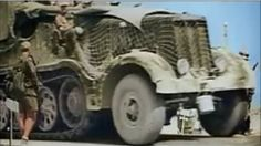 A Afrika Korps Famo SdKfz 9, with a interesting camo net over the engine hood area, moving at speed past walking ground troops.