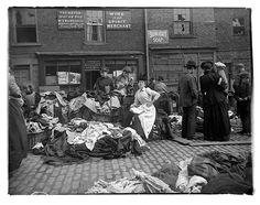 """A secondhand clothes seller at Newcastle cloth market reads as customers inspect her goods. A set of original glass negatives showing street scenes of century Newcastle found by Aaron Guy, who works at the city's Mining Institute. Victorian Street, Victorian London, Victorian Era, Victorian History, East End London, Old London, Old Pictures, Old Photos, Vintage Photographs"