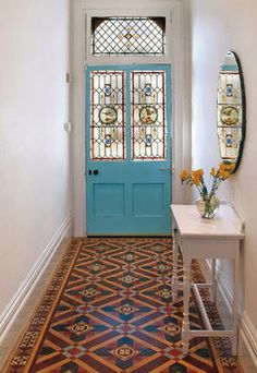 Turquoise blue painted front door with decorative / patterned tile floor
