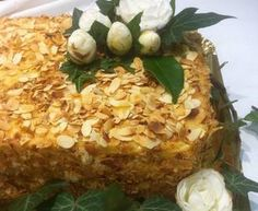 Bolo pão de ló de água, com recheio de massa folhada e creme ligeiro de ovos, com cobertura de lascas de amêndoa e laterais de migalhas de massa folhada.