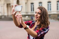Stock photo - young girl take selfie from hands with phone on summer city street urban concept