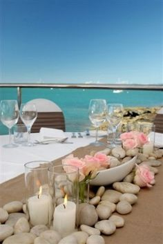 Easy beach centerpiece idea with rocks, candles & flowers.