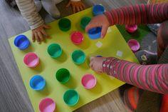 Petit jeu de manipulation. SCRAAAATCH !on peut faire des jeux d'association de couleur (plaque bleue pour bouchons bleus, plaque rose pour bouchons rose...). On peut aussi coller des gommettes dans les bouchons et les scatcher par paires.