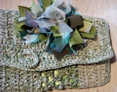 pochette di cotone di color melange verde/ecru, realizzata a uncinetto e decorata con nastri di tessuti pregiati tagliati a vivo e annodati uno ad ...
