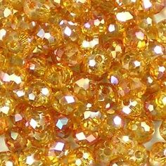 Topaz AB Lustre 4mm x 3mm small facetted glass rondelle beads. Transparent light gold, with an iris rainbow shimmer. UK seller.