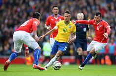 Neymar of Brazil controls the ball as Gonzalo Jara (L) and Gary Medel (R) of Chile close in during the international friendly match between Brazil and Chile at the Emirates Stadium on March 29, 2015 in London, England.