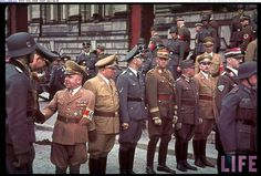 A photo conveying the mind boggling variety of uniforms, insignia and decorations prevalent during Nazi times. Light brown marks high NSDAP (National Socialist Party) officers; note the dwarfish man with the missing arm wearing the armband and collar insignia signifying the rank of Reichsleiter (National Leader). Himmler is there in his field gray SS uniform. Right next to him a ranking SA officer in his dark brown uniform and next to him an officer of the German Labor Front.