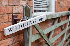 Wooden 'wedding' direction sign - Image by Ali Lovegrove Photography - A wedding at Halstead House with a pink and grey colour scheme and the groom wearing Ted Baker with photography by Ali Lovegrove Photography