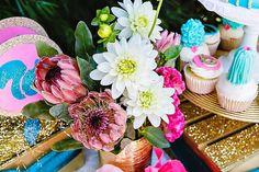 mesa de doces com bandeirolas para festa infantil para meninas tema animais da floresta em tons de azul, rosa e dourado. Flores em rosa e branco.