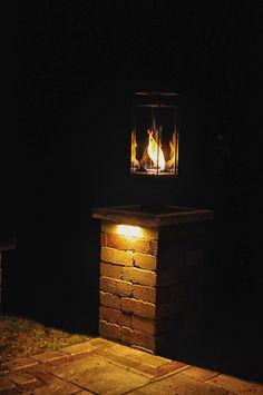 Tempest Torch Gas Lantern Sitting On Top Of Stone Pillar