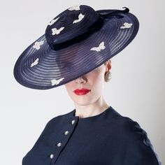 Charming World War Two era tilt topper hat dates to the late 1930s or early 1940s. Navy blue horsehair hat features a large see thru brim allowing for maximum tiltability. Trimmed with crocheted butterflies studded with rhinestones and a midnight blue velvet ribbon that ties in a large bow in back. Comes with a short glass head hat pin for affixing the back of this hat to your coiffure.