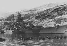Fine and relatively unknown view of 15 in Tirpitz (sister to Bismarck) in the Norwegian setting typical of her war. As a threat in being to the Arctic convoys she was constantly attacked by the British, finally being finished off by RAF Lancasters using 12000 lb 'Tallboy' bombs in November 1944: she had already been severely damaged in earlier raids.